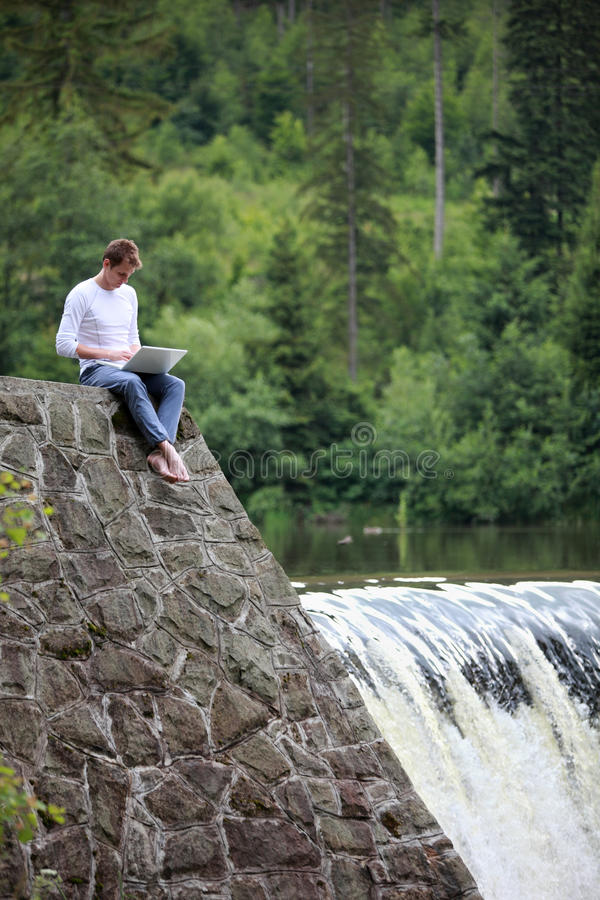 有坐在瀑布的笔记本的人 库存图片