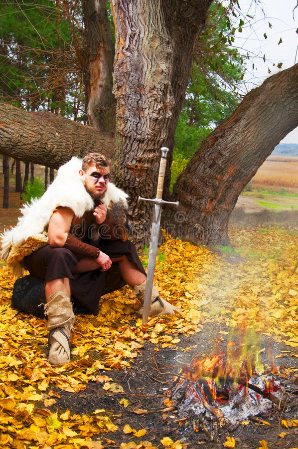 有坐在火附近的剑的肌肉古老战士 免版税图库摄影