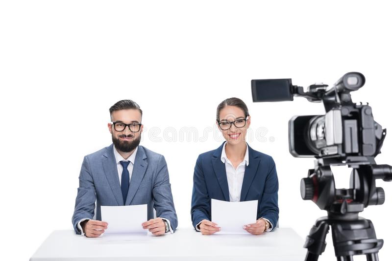 有坐在照相机前面的纸的两个微笑的新闻广播员, 免版税库存图片