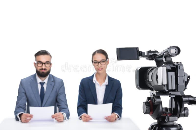 有坐在照相机前面的纸的两个新闻广播员, 免版税图库摄影