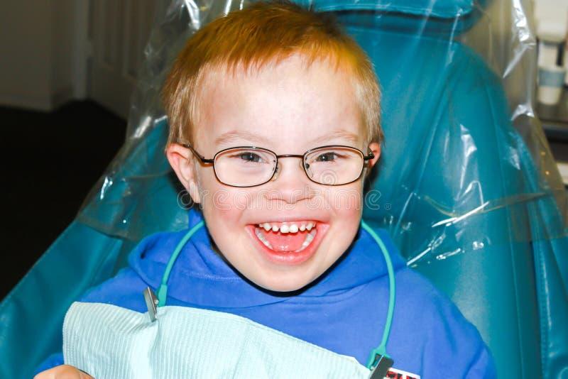 有坐在牙医椅子的下来综合症状的男孩 免版税图库摄影