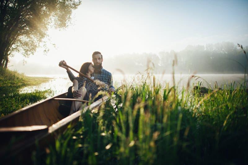 有坐在独木舟的丈夫的妻子在早晨 免版税库存图片