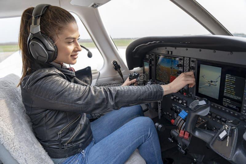 有坐在现代飞机客舱的耳机的美丽的微笑的妇女飞行员  免版税图库摄影