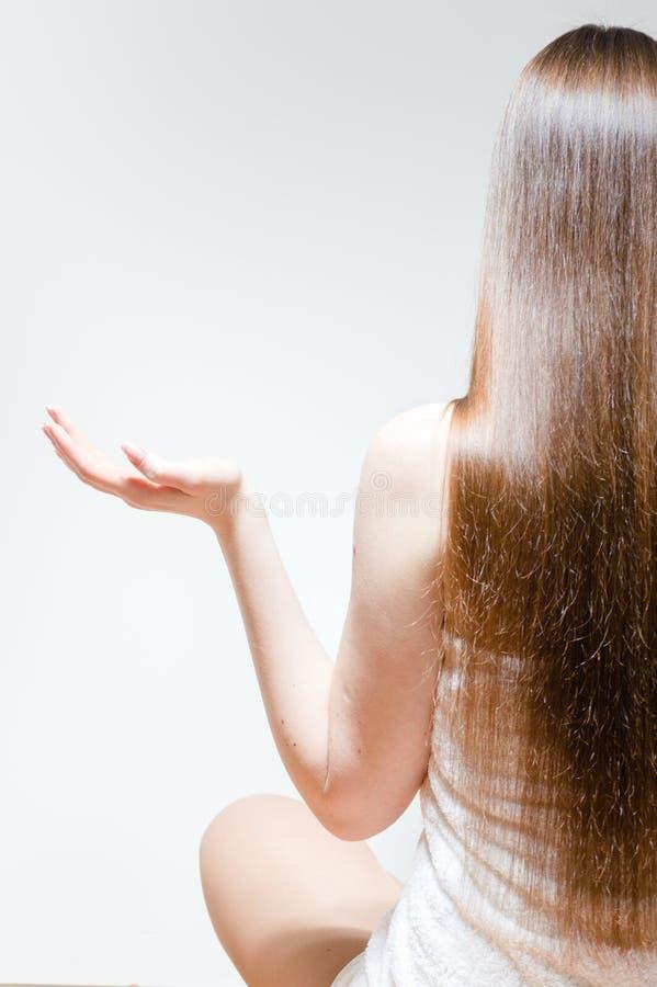 有坐在瑜伽姿势放松的长的美丽的头发的少妇 免版税图库摄影