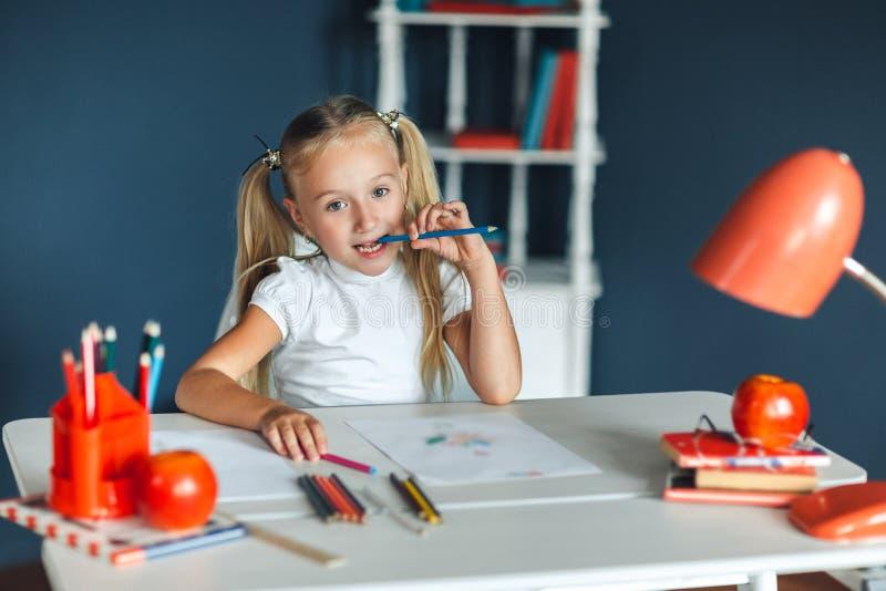 有坐在白色桌上和拿着在她的嘴的金发的滑稽的女孩紫色铅笔 免版税图库摄影