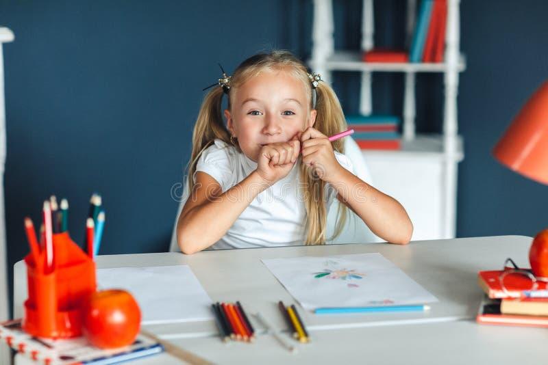 有坐在白色桌上和拿着紫色铅笔的金发的滑稽的女孩 库存图片