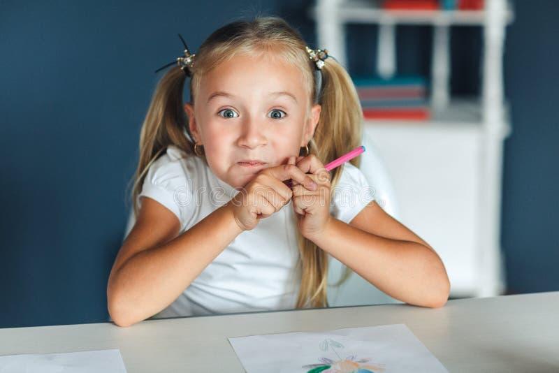 有坐在白色桌上和拿着紫色铅笔的金发的滑稽的女孩 库存照片