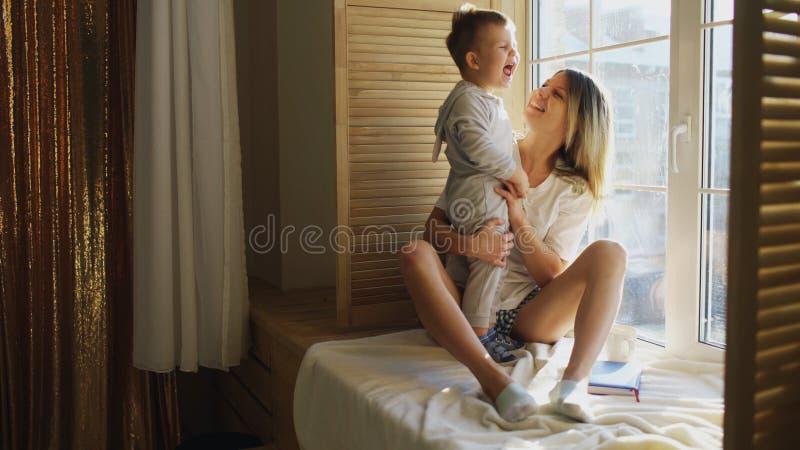 有坐在窗口和戏剧的婴孩的母亲 免版税库存图片