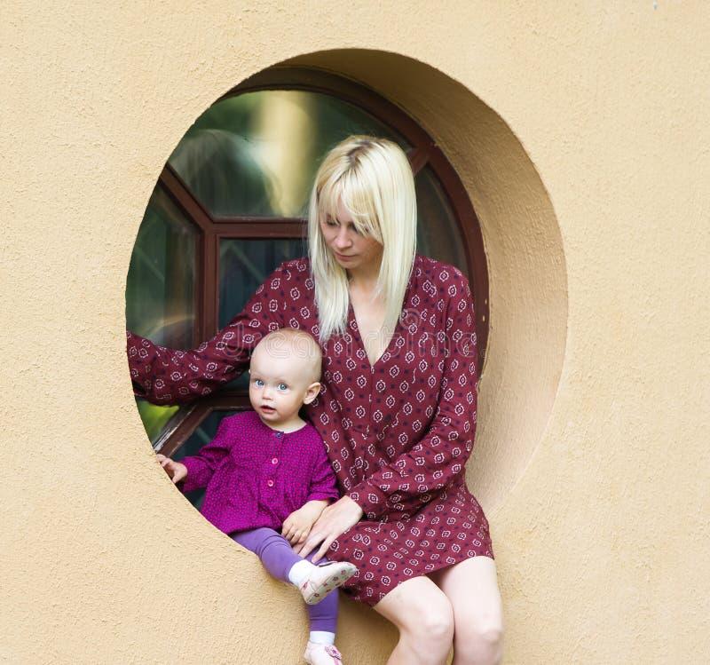 有坐在窗口的婴孩的母亲 免版税库存照片