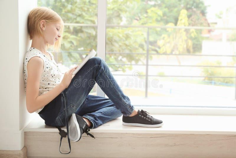 有坐在窗口附近的片剂的逗人喜爱的少年女孩 库存图片