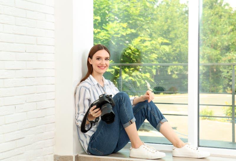 有坐在窗口附近的现代照相机的专业摄影师 免版税图库摄影