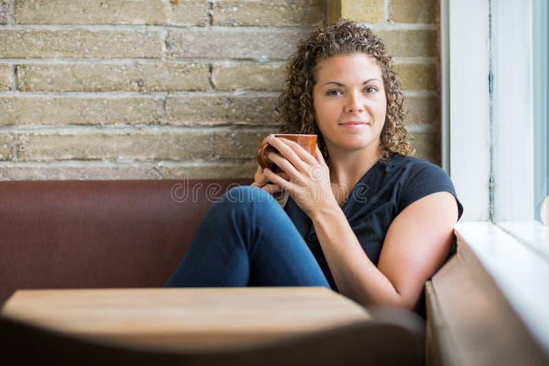 有坐在自助食堂的咖啡杯的妇女 图库摄影