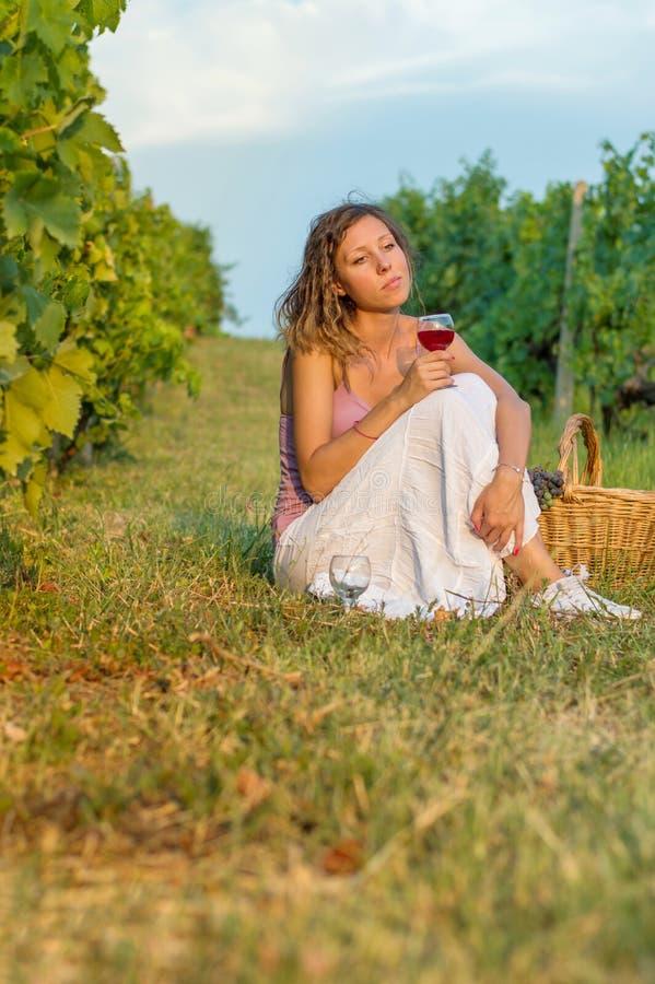 有坐在葡萄园里的酒杯的女孩 免版税库存照片