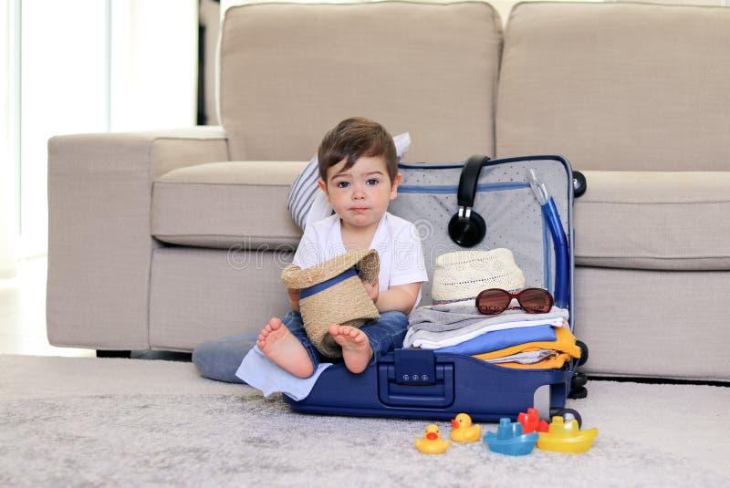 有坐在蓝色手提箱藏品草帽的滑稽的面孔表示的逗人喜爱的矮小的男婴在手上,包装在假期, 免版税库存照片