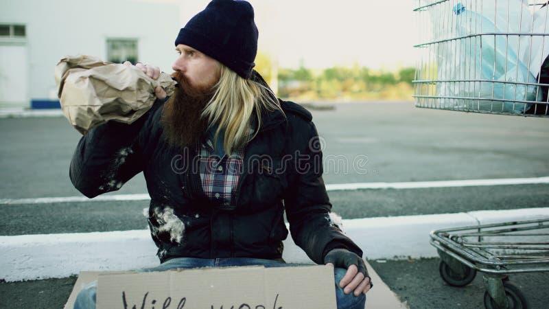有坐在购物车和饮料酒精附近的纸板的有胡子的年轻无家可归的人冷的天 免版税图库摄影