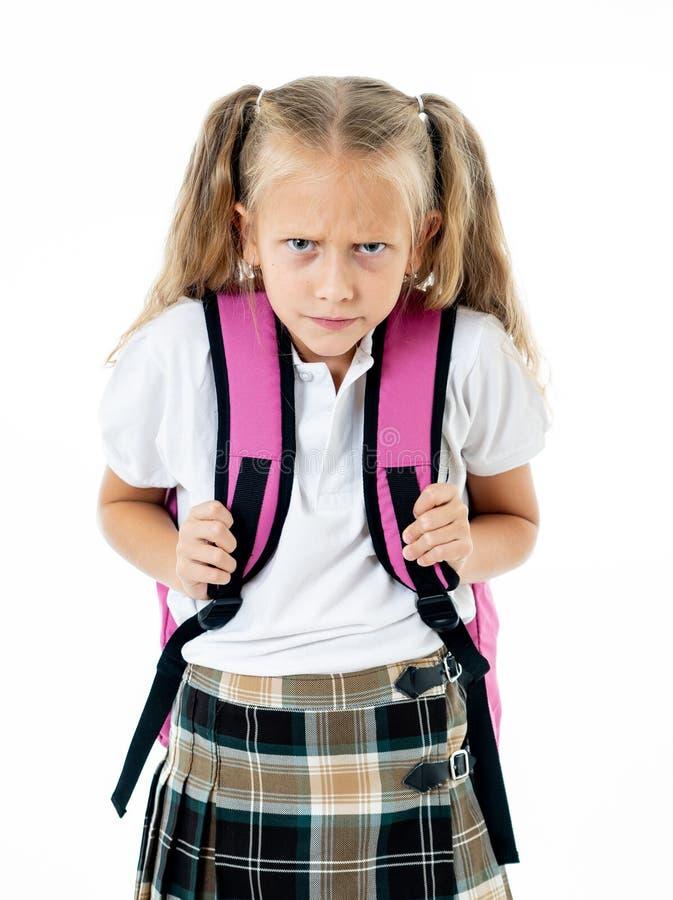 有坐在重音的金发的哀伤和疲乏的逗人喜爱的女小学生做家庭作业淹没与许多项研究和课本 库存照片