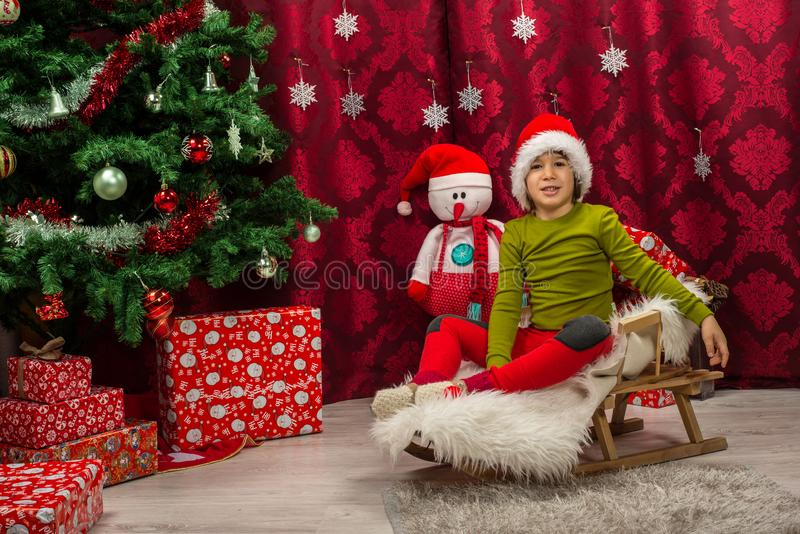 有坐在雪橇的圣诞老人帽子的小男孩 免版税库存图片