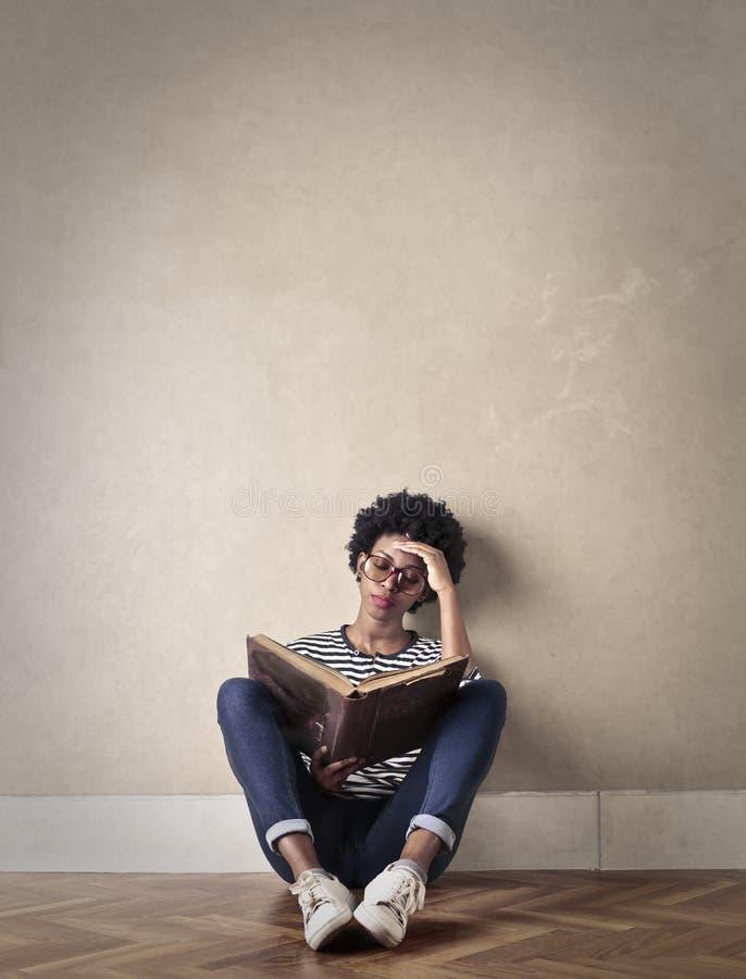 有坐在靠窗座位读书的长的头发的少妇 库存照片