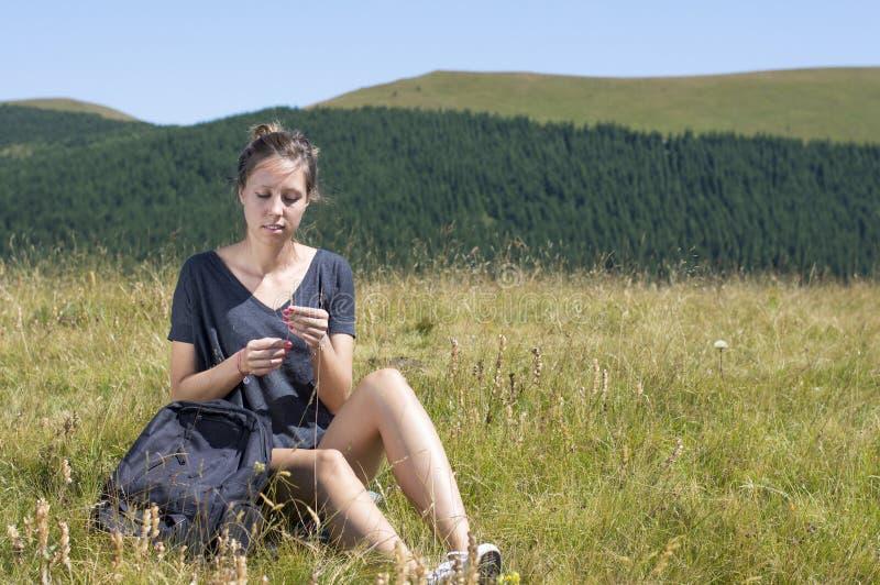 有坐在领域和golding st的背包的少妇 免版税图库摄影