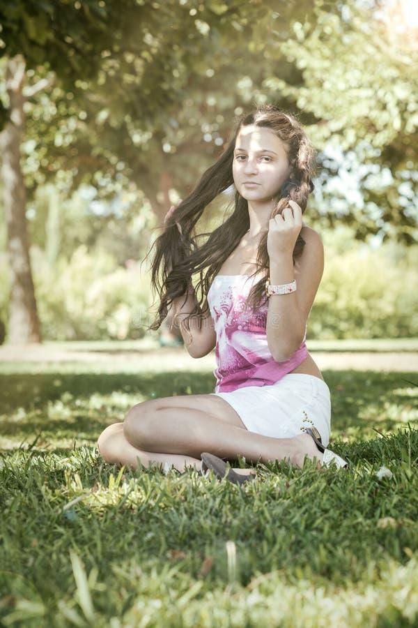 有坐在领域的长的头发的女孩 免版税库存图片