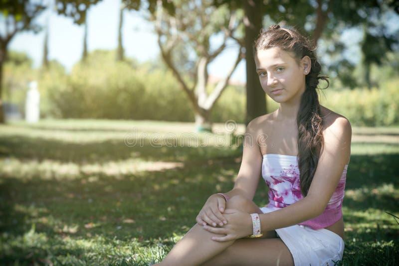 有坐在领域的长的头发的女孩 免版税库存照片