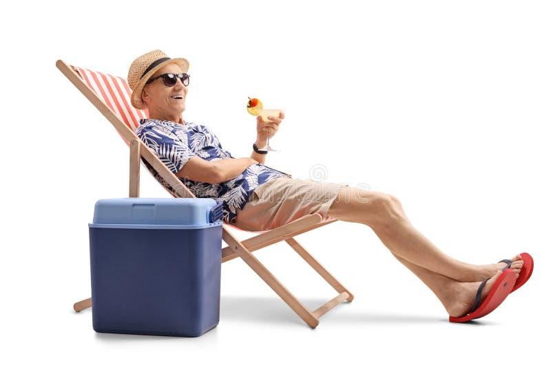 有坐在轻便折叠躺椅的鸡尾酒的年长游人 库存图片