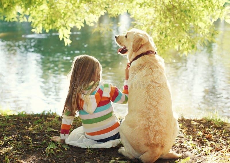 有坐在晴朗的夏天的拉布拉多猎犬狗的小孩 免版税库存图片
