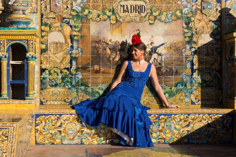 有坐在Plaza de西班牙的蓝色佛拉明柯舞曲礼服的妇女 图库摄影