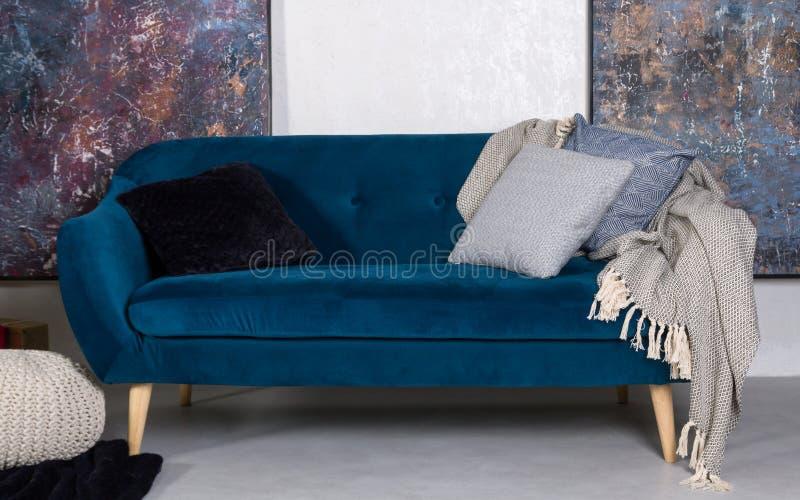 有坐垫和灰色毯子的水军蓝色减速火箭的沙发 库存图片