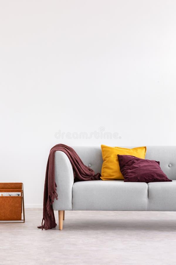 有坐垫的灰色长沙发在白色最小的客厅内部与在墙壁上的拷贝空间 实际照片 免版税库存照片