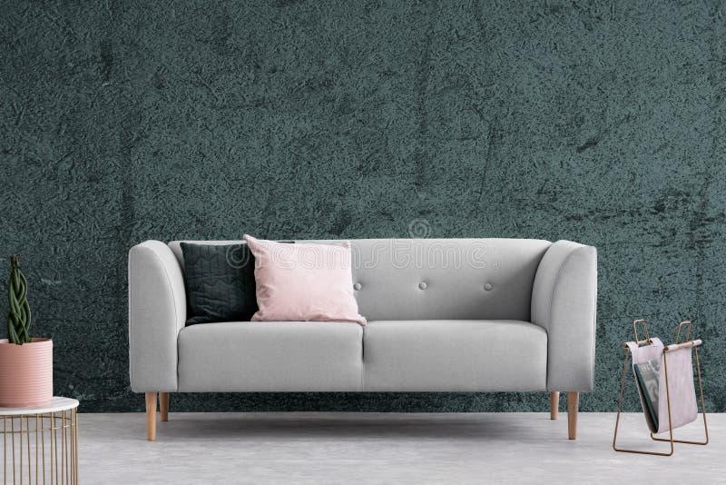 有坐垫的灰色长沙发在黑暗的公寓内部与织地不很细墙壁 实际照片 库存图片
