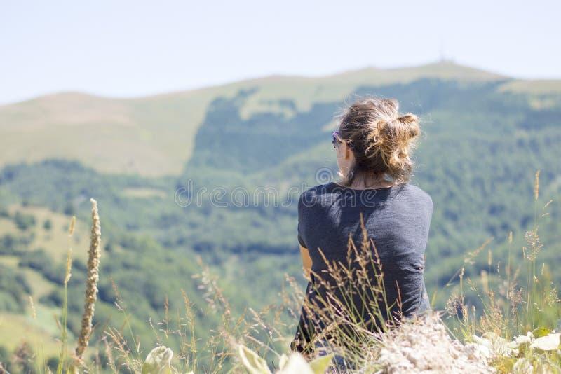 有坐峭壁的边缘和看的背包的少妇 免版税库存照片