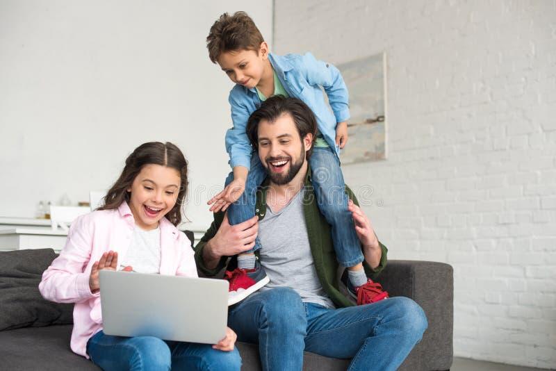 有坐沙发和使用膝上型计算机的两个逗人喜爱的孩子的愉快的父亲 库存照片