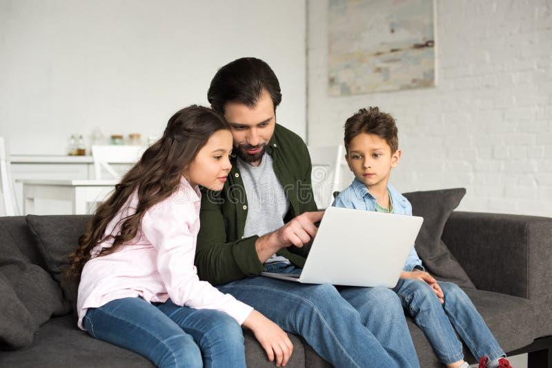 有坐沙发和使用膝上型计算机的两个逗人喜爱的孩子的父亲 库存图片