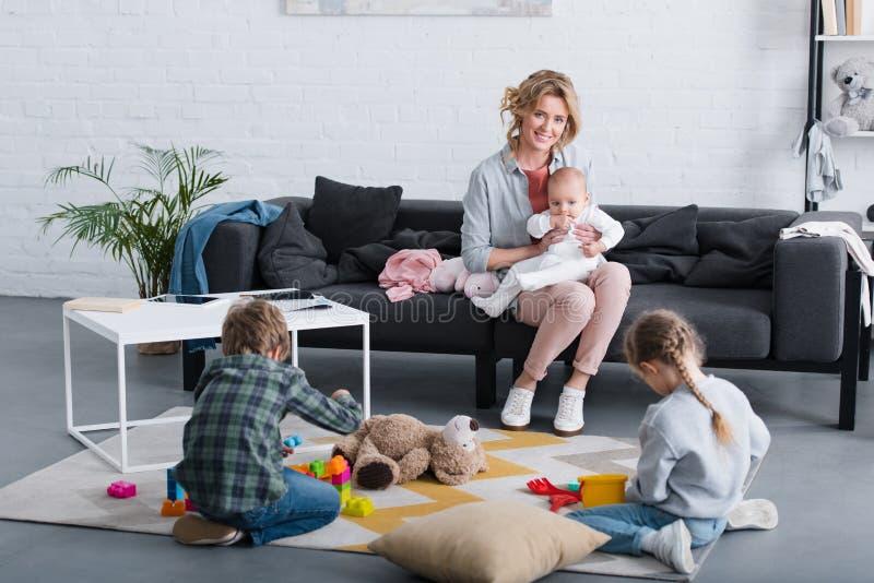 有坐沙发和微笑对照相机的婴儿孩子的愉快的母亲,当兄弟姐妹使用时 向量例证