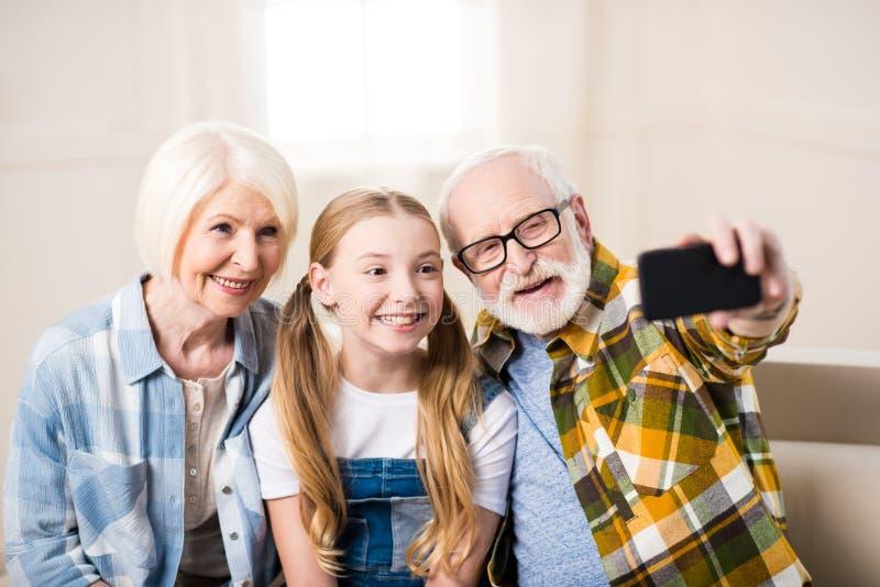 有坐沙发和采取selfie的祖母和祖父的女孩 免版税库存图片