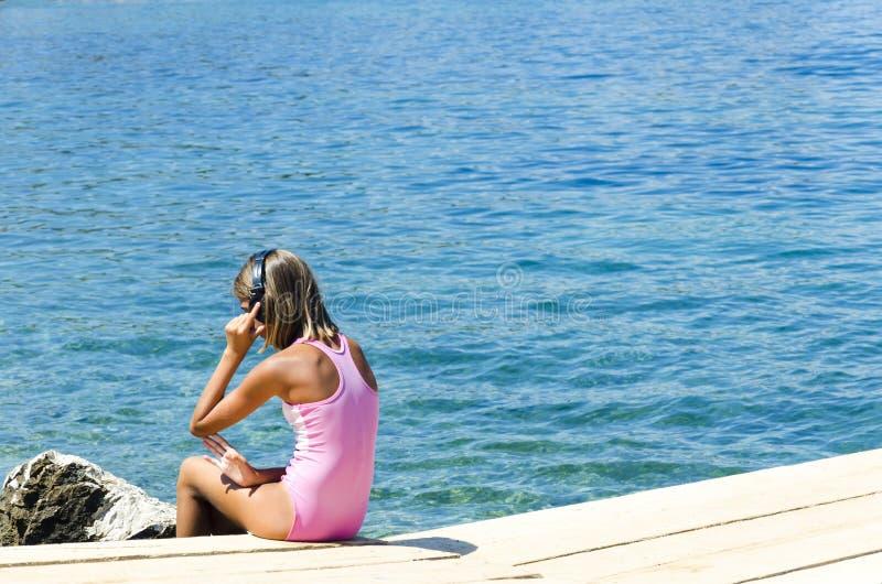 有坐河停泊处和听到音乐的耳机的阿皮女孩在夏天 免版税图库摄影