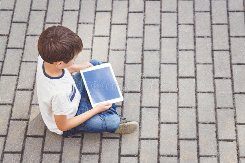 有坐片剂的计算机的孩子户外 教育,学会,技术,朋友,学校概念 顶视图 免版税库存照片