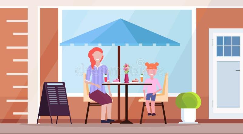有坐现代夏天咖啡馆饮用的鸡尾酒和吃蛋糕街道餐馆大阳台的女儿的母亲室外 皇族释放例证