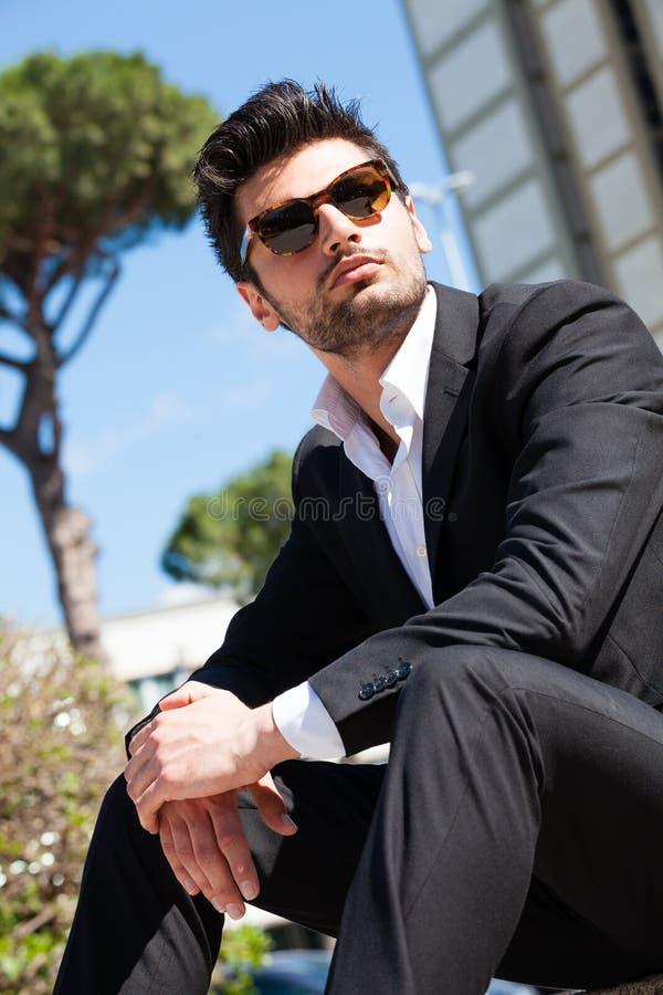 有坐的太阳镜的英俊和迷人的年轻人户外 免版税库存图片