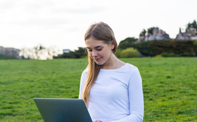 有坐的膝上型计算机和的书的年轻美丽的女孩学生和 免版税图库摄影