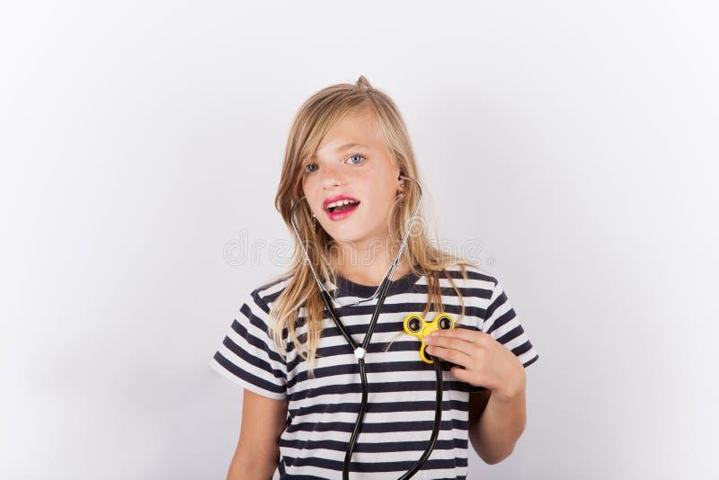 有坐立不安锭床工人的女孩作为听诊器-健康概念 库存照片
