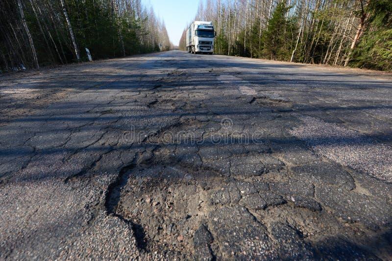 有坑洼的高速公路 质量差路面进入它的破坏主要阶段  在路汽车上 库存照片
