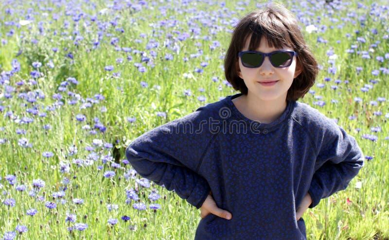 有坚定的手势的快乐的少女在花卉背景 免版税库存图片