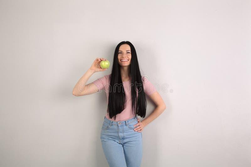 有坚持灰色背景佩带的蓝色牛仔裤和桃红色衬衣微笑的长发的年轻可爱的深色的妇女 免版税库存图片