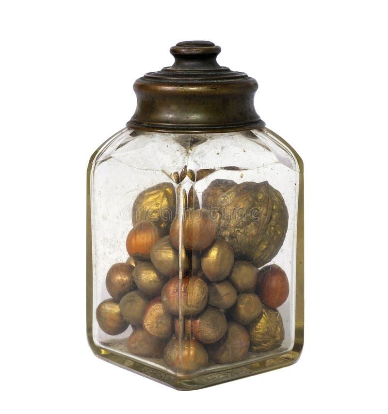 有坚果和榛子的老瓶子在白色背景 免版税库存照片