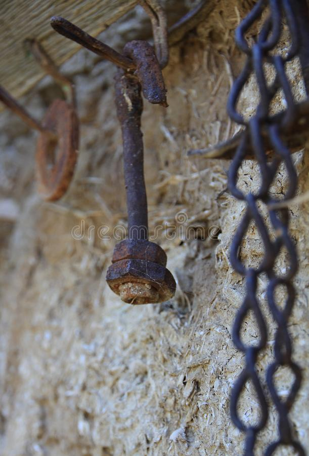 有坚果的生锈的弯曲的螺栓在一个老挂衣架勾子 库存图片