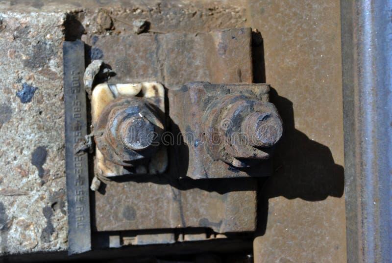 有坚果的生锈的螺栓铁路路轨,被击碎的石头金属表面上  免版税库存图片