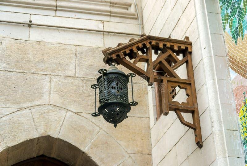 有垂悬从在一个老教会的一个石墙上的一个木制框架的十字架的老铁灯笼 库存图片
