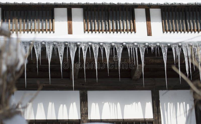 有垂悬从屋顶的长的冰柱的高山房子 长野,日本 免版税图库摄影